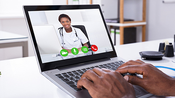 person typing on a laptop in a virtual consultation with a doctor