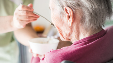Person feeding a senior person