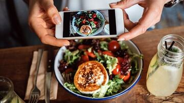 student taking photo with phone of a delicious meal