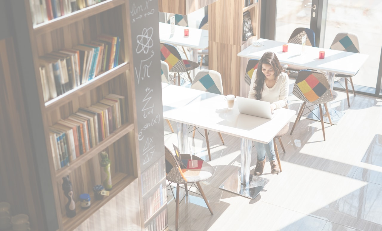 Student sitting at a table studying in a library