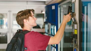teen boy paying with mobile phone at vending machine