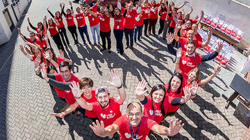 Community members stand in a heart formation to raise awareness for the Stop Hunger network