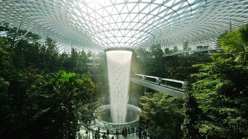 train travelling through giant greenhouse filled with trees, a waterfall at the center